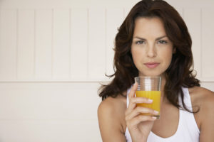 woman-holding-a-glass-of-orange-juice-and-looking-skeptical